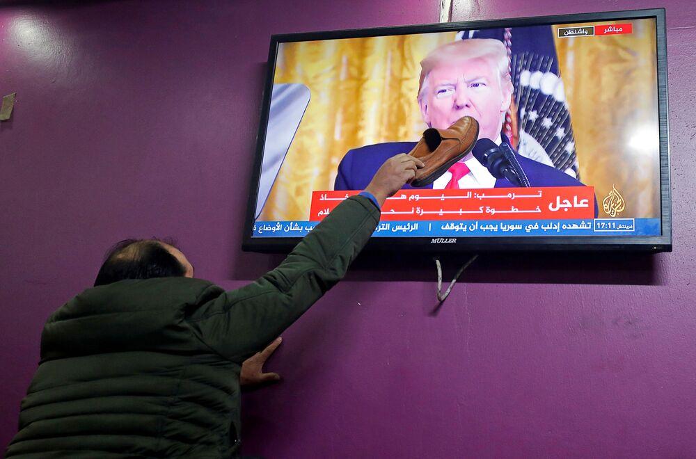 Palestino põe sapato em uma tela de televisão enquanto o presidente americano, Donald Trump, anuncia seu plano de paz para o conflito israelense-palestino em uma cafeteria em Hebron, na Cisjordânia ocupada por Israel