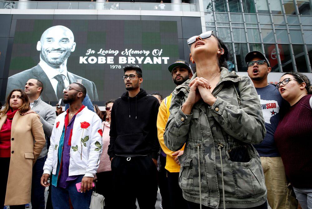 Fãs do jogador de basquetebol Kobe Bryant se aglomeram ao lado da imagem do jogador após a estrela do clube de basquetebol Los Angeles Lakers morrer em um acidente de helicóptero em Los Angeles, EUA