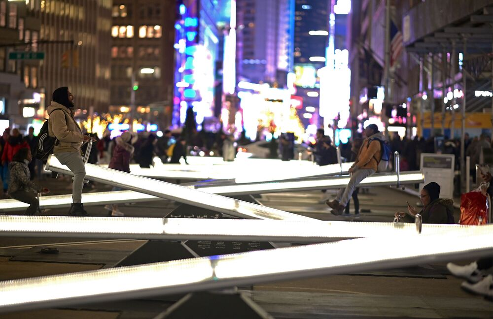 Populares se divertem em gangorras iluminadas na Broadway, próximo da Time Square em Nova York, EUA