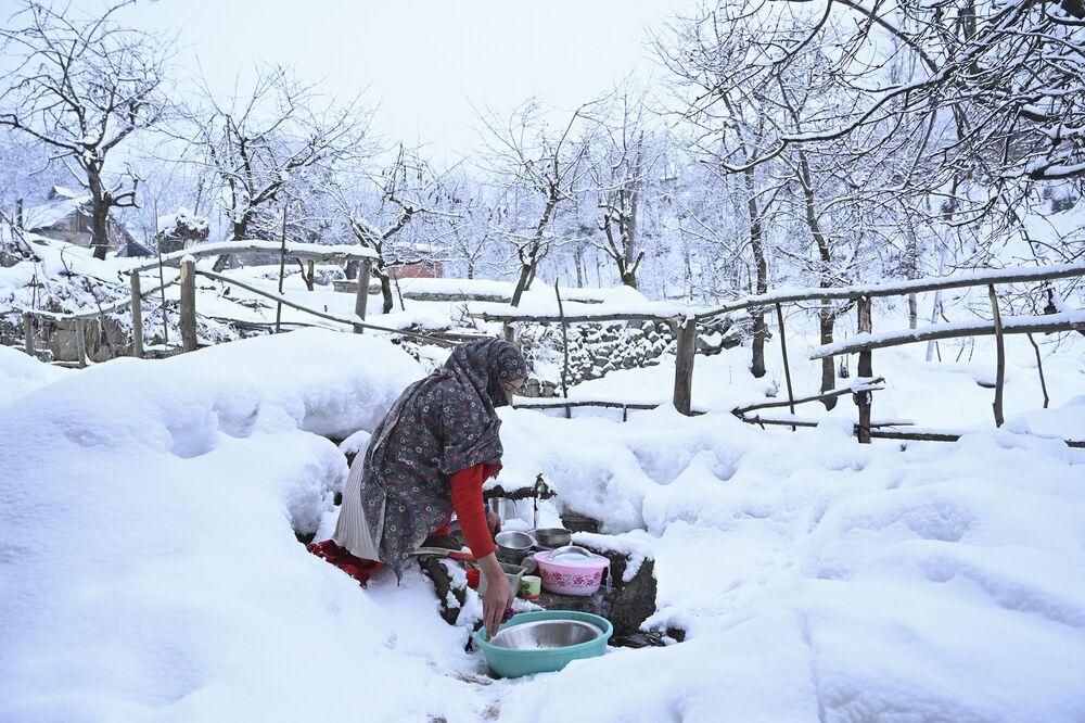 Mulher lava louça após neve cair em Srinagar, na Caxemira