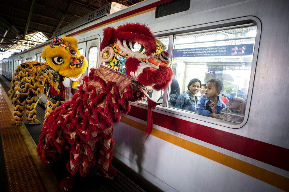 Passageiros observam foliões com fantasias de leão durante o Ano Novo lunar chinês em Jacarta, Indonésia