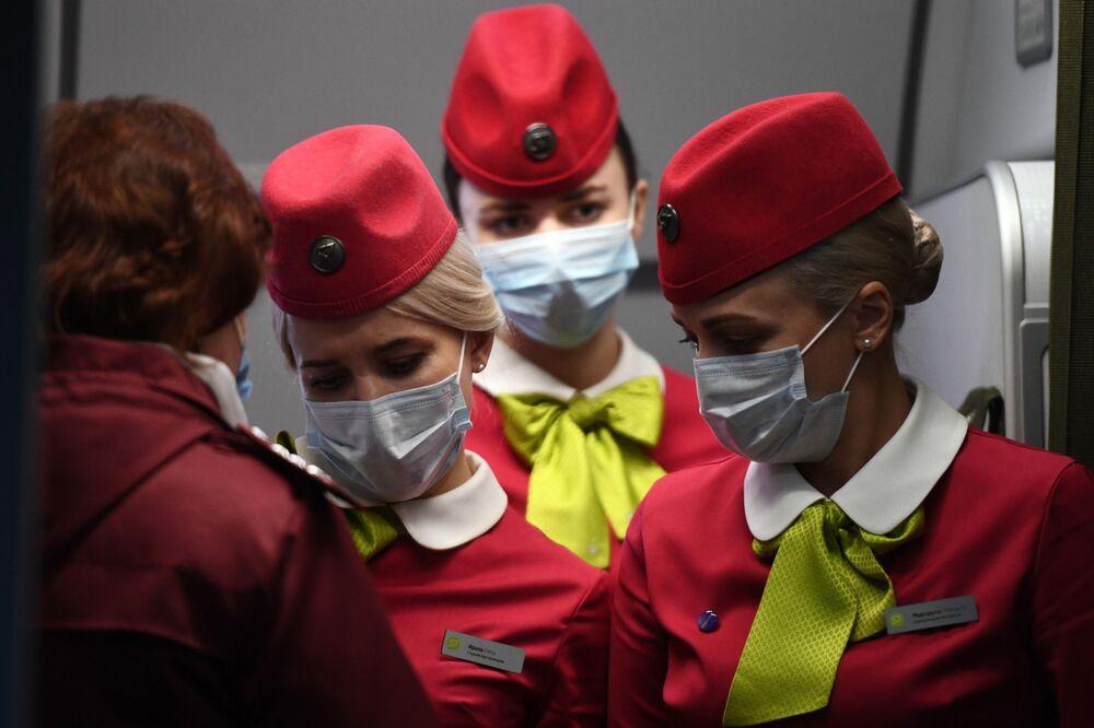 Aeromoças da companhia aérea russa S7 usando máscaras em voo chegando de Pequim ao Aeroporto de Tolmachevo, na cidade russa de Novossibirsk