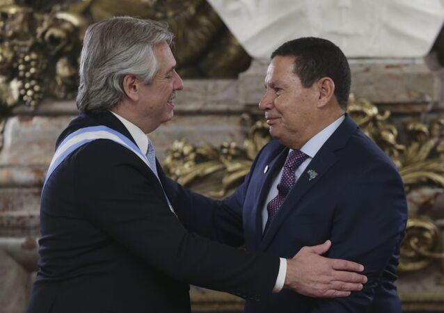 O presidente da Argentina, Alberto Fernández, à esquerda, cumprimenta o vice-presidente do Brasil, Hamilton Mourão, durante a cerimônia de posse do presidente argentino.