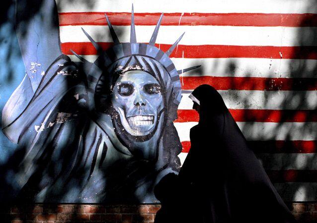 Mulher passa por muro grafitado da antiga embaixada dos EUA em Teerã, capital do Irã (foto de arquivo)