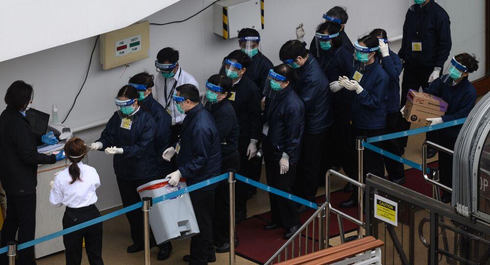 Membros do Departamento de Saúde de Hong Kong fazem fila para limpar as mãos no convés do navio de cruzeiro World Dream (foto de arquivo)