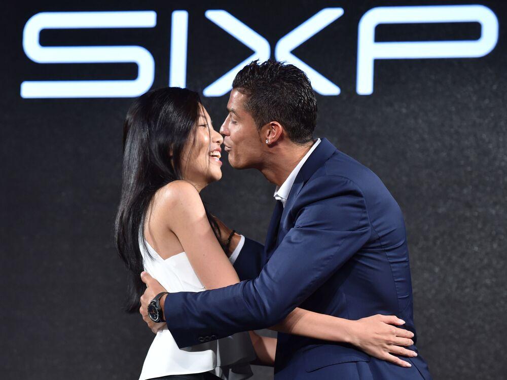 O jogador Cristiano Ronaldo beija uma fã em um evento promocional