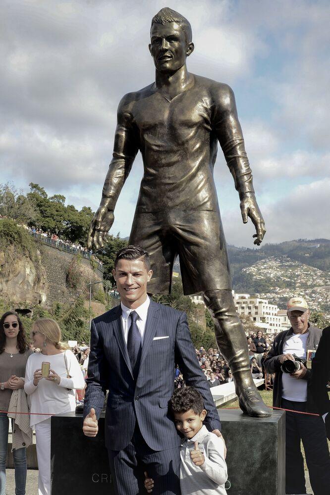 Cristiano Ronaldo com seu filho diante de sua estátua em sua cidade natal, Funchal, em Portugal