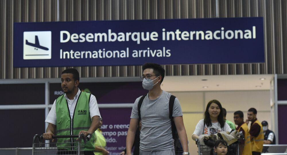 Turistas e funcionários do Aeroporto Internacional Tom Jobim, também conhecido como Aeroporto do Galeão, na zona norte do Rio de Janeiro, usam máscaras para prevenir o contágio com o coronavírus. Turistas chineses desembarcam todos os dias no Brasil.