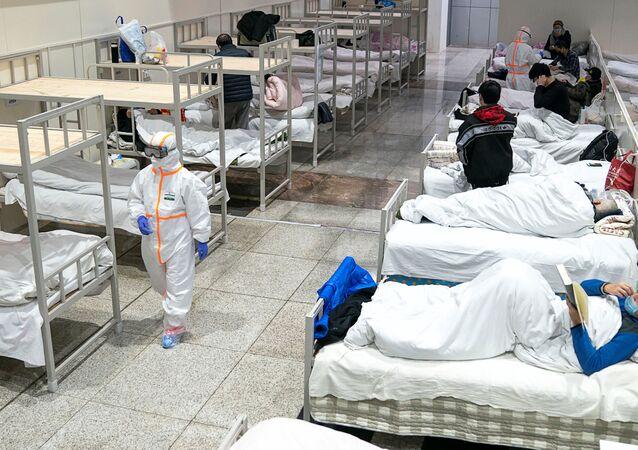 Médicos em trajes de proteção atendem pacientes em um hospital improvisado em Wuhan, província de Hubei, China, 5 de fevereiro de 2020