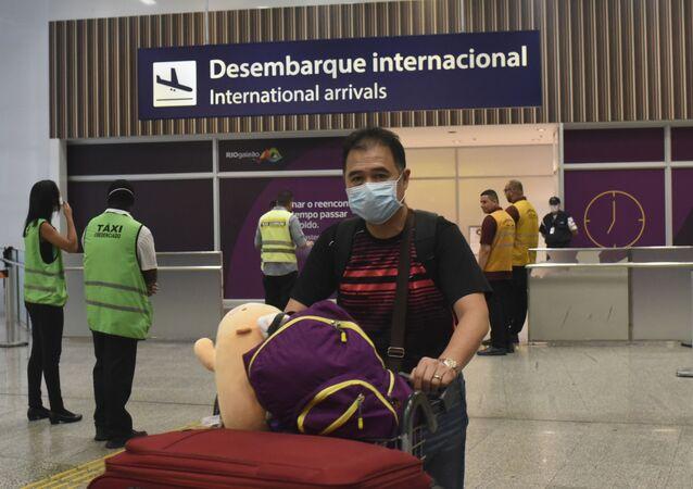 Turistas e funcionários do Aeroporto Internacional Tom Jobim, no Rio de Janeiro, usam máscaras para prevenir o contágio com o coronavírus