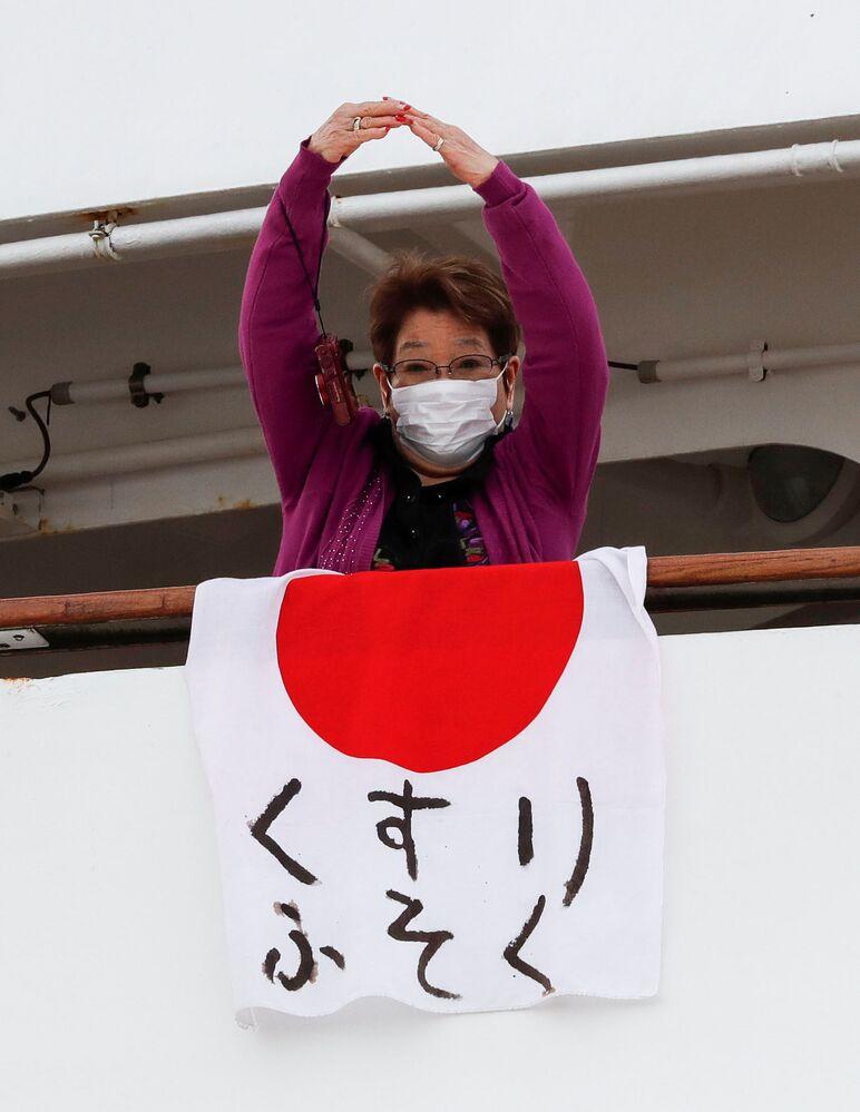 Paciente pendura a bandeira japonesa com a mensagem medicamentos em falta, no navio Diamond Princess, colocado em quarentena em função do coronavírus
