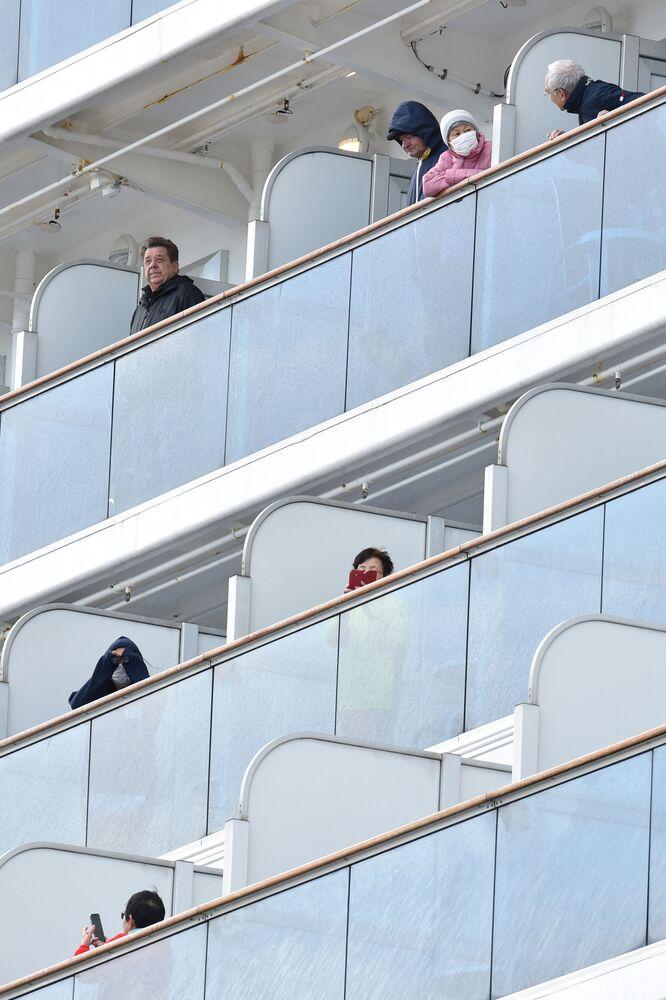 Passageiros do cruzeiro Diamond Princess que está em quarentena observam o porto de Yokohama