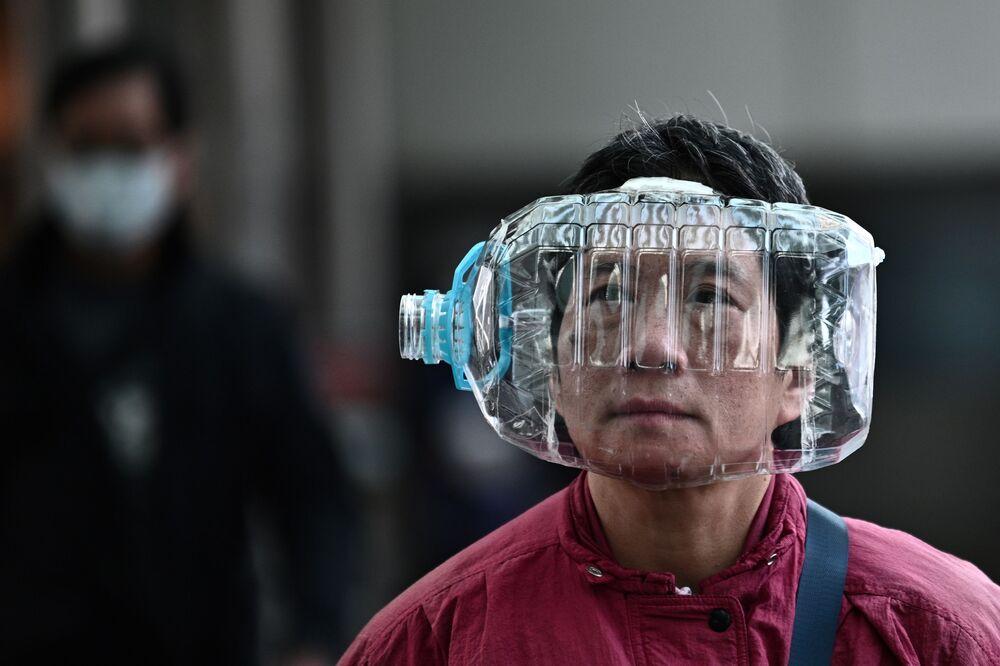 Homem em Hong Kong usa garrafa plástica como máscara para se proteger do coronavírus
