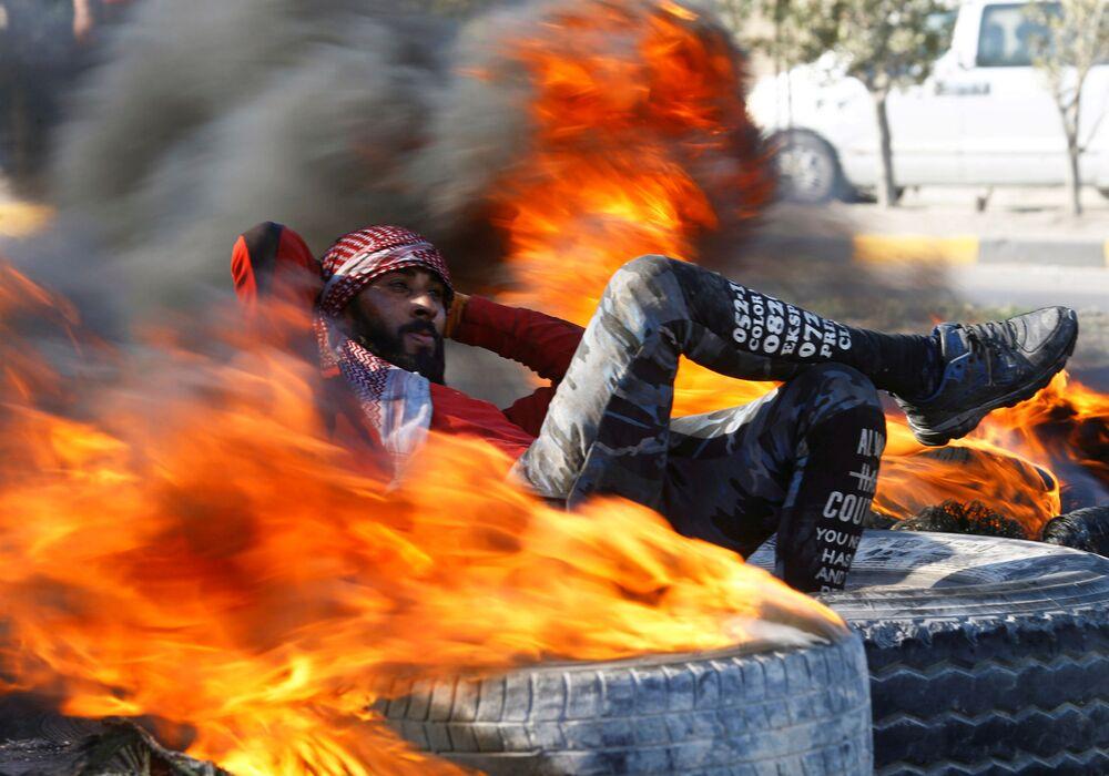 Manifestante iraquiano senta entre pneus em chamas tentando bloquear uma via pública durante protesto antigovernamental em Najaf, Iraque