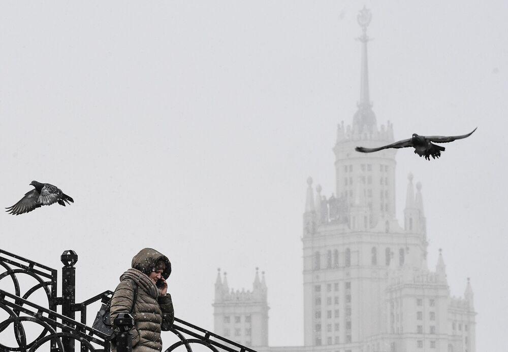 Mulher em ponte sobre o rio Yauza, em Moscou, falando ao telefone com uma das Torres de Stalin em fundo
