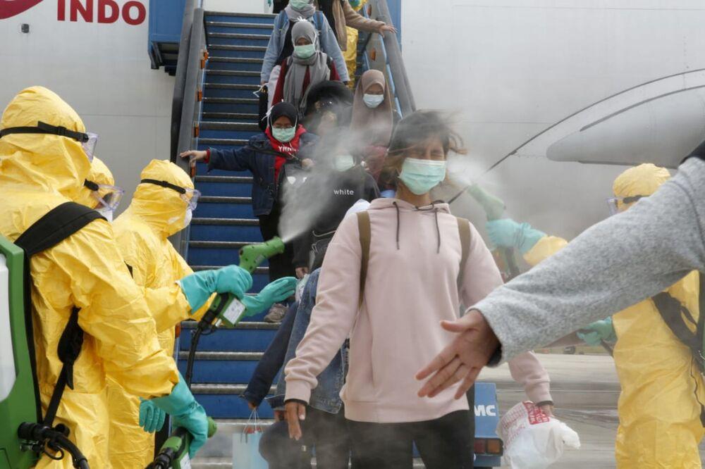 Agentes da Saúde da Indonésia usam borrifador antisséptico em passageiros de voo oriundo da cidade chinesa de Wuhan