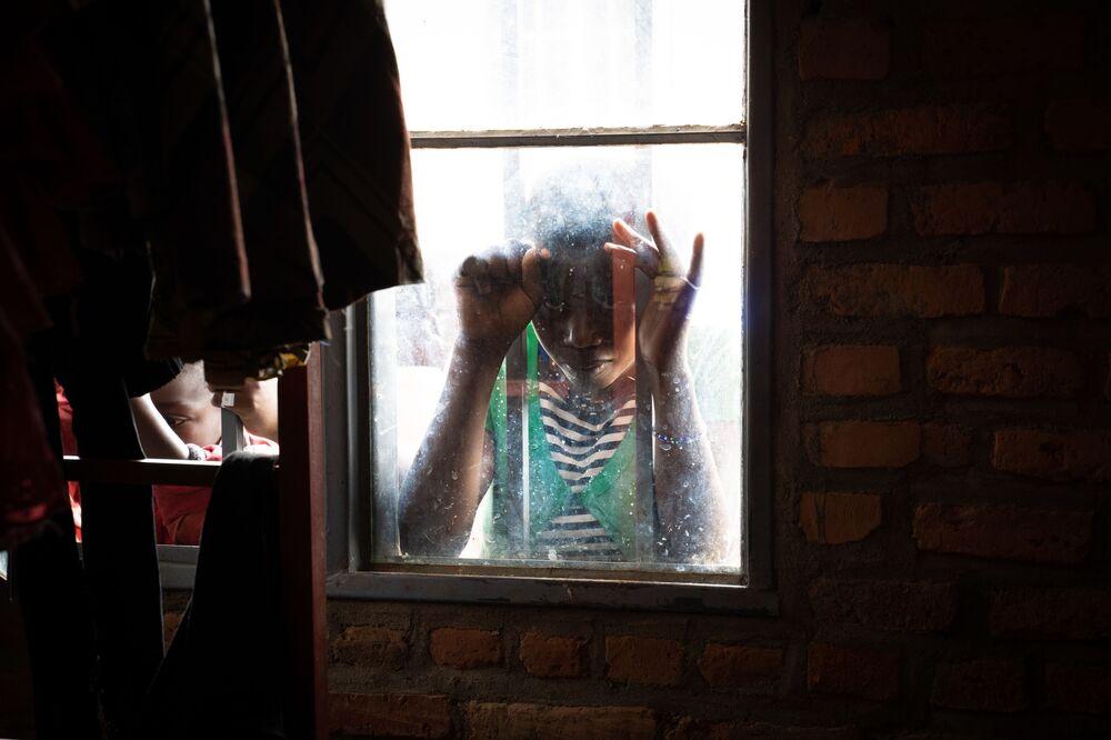 Menina olha por janela no centro de repatriados de Nyarushishi, Ruanda, para familiares de ex-rebeldes do país transferidos da República Democrática do Congo