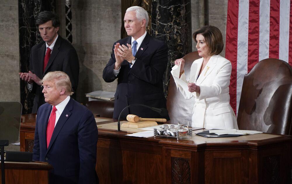 Presidente da Câmara de Representantes dos EUA, Nancy Pelosi, rasga folhas com o discurso do presidente dos EUA, Donald Trump, ao lado do vice-presidente do país, Mike Pence, no Capitólio de Washington