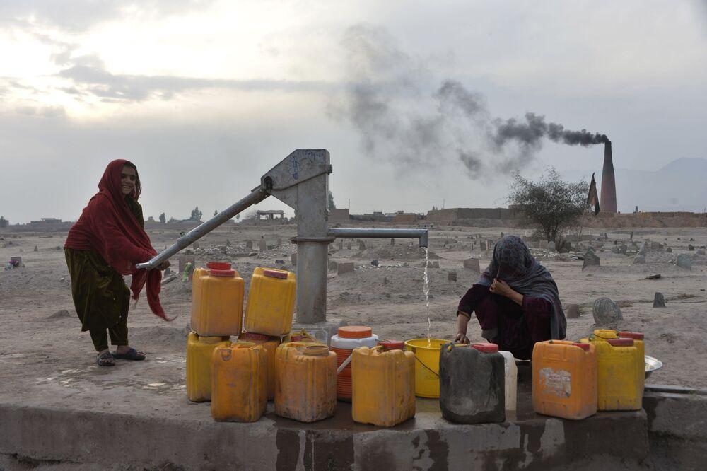 Mulheres coletam água de poço aos arredores da cidade afegã de Jalalabad