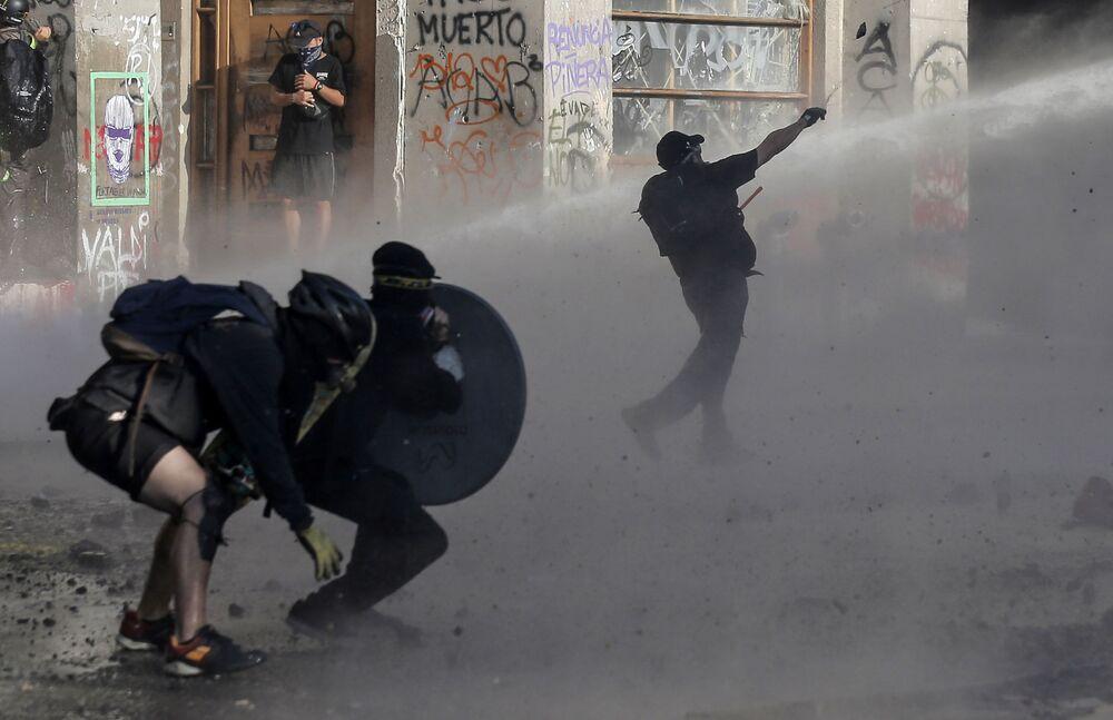 Manifestantes em embates com a polícia durante protesto contra o presidente chileno, Sebastián Piñera, na capital do país, Santiago