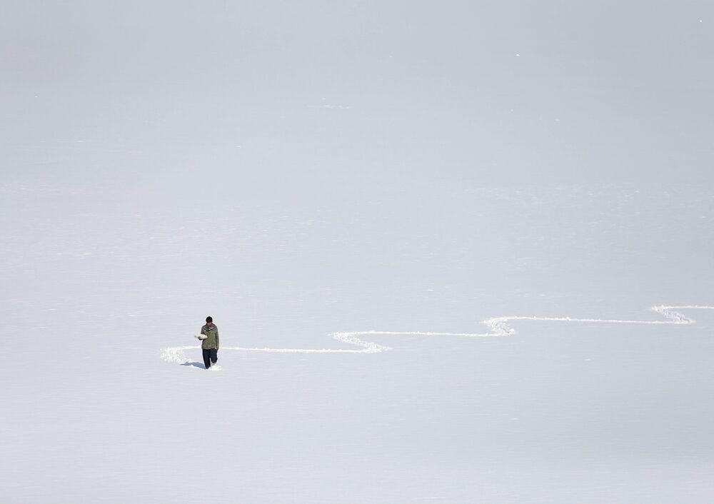 Afegão carrega ovos cozidos para vender enquanto caminha sobre a neve no lago de Qargha na capital Cabul