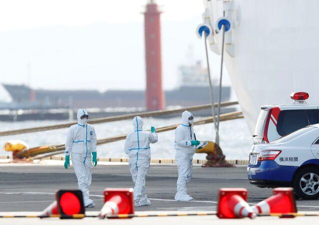 Em Yokohama, no Japão, trabalhadores usando proteção se preparam para transferir passageiros com coronavírus do navio Diamond Princess para um hospital.