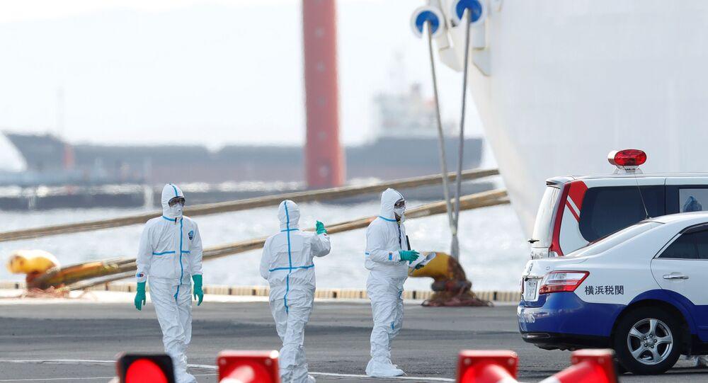Em Yokohama, no Japão, trabalhadores usando proteção se preparam para transferir passageiros com coronavírus do navio Diamond Princess para um hospital (arquivo)