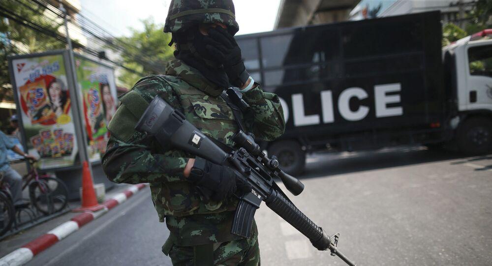 Um policial armado em frente a um caminhão da polícia na Tailândia.