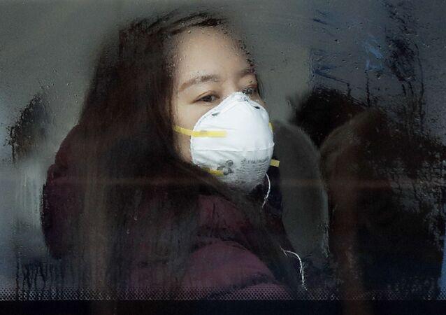 Mulher usa máscara de proteção em ônibus, na capital chinesa Pequim (foto de arquivo)