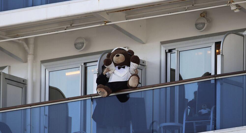 Mulher segura urso de pelúcia no balcão do cruzeiro Diamond Princess