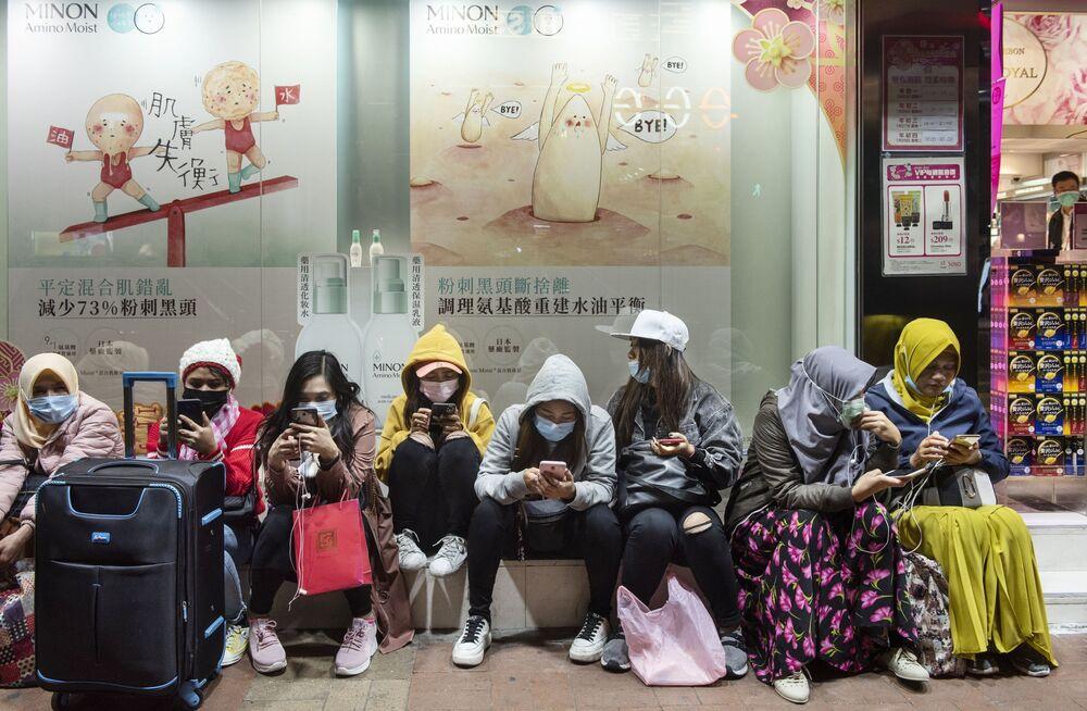 Mulheres usando máscaras em rua de Hong Kong