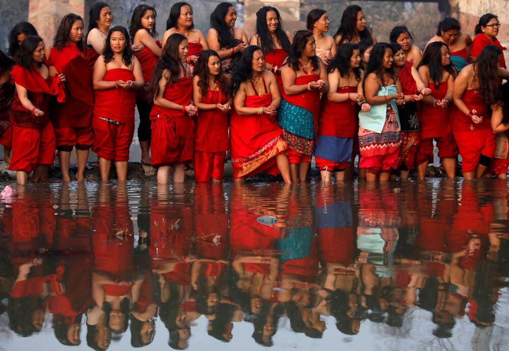 Mulheres devotas realizam rito hindu no rio Hanumante durante o festival Swasthani Brata Katha, no Nepal