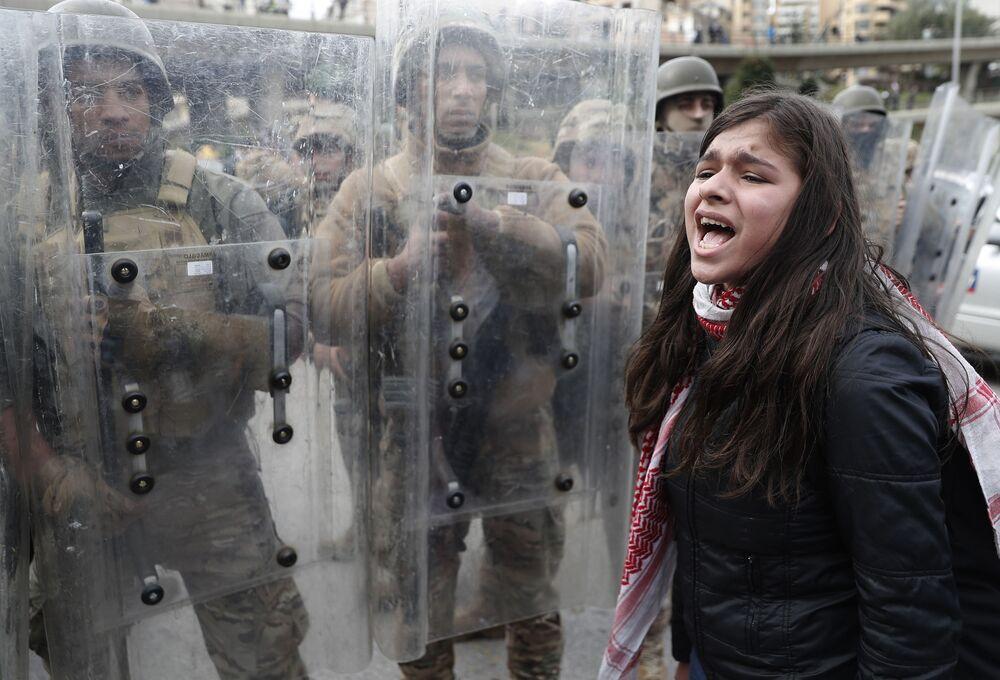 Jovem grita slogans durante protestos contra o governo libanês diante de soldados do país perto do prédio do parlamento local, na capital Beirute