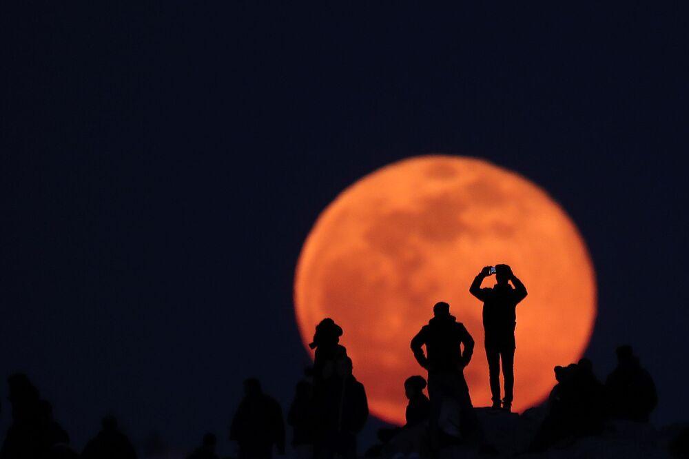 Populares apreciam a lua cheia na colina do Areópago no sítio arqueológico de Acrópole em Atenas, Grécia