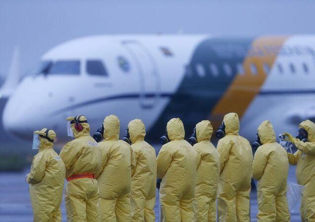 Soldados brasileiros com roupas de proteção biológica esperam repatriados oriundos de Wuhan na base aérea de Anápolis