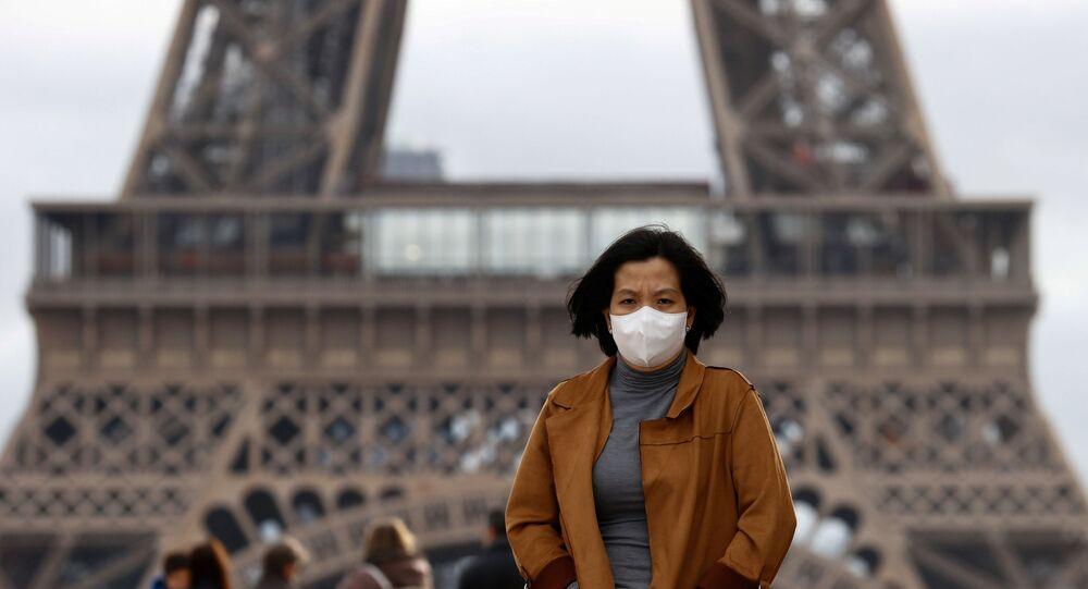 Mulher protege o rosto contra infecções na esplanada Trocadero, na frente da Torre Eiffel, em Paris, na França, em 1 de fevereiro de 2020