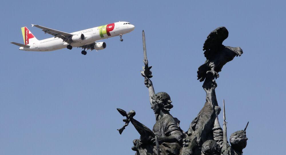 Avião da companhia aérea portuguesa TAP sobrevoa o monumento aos heróis da Guerra Peninsular, em Lisboa, Portugal