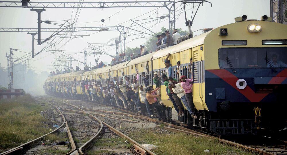 Passageiros indianos se penduram nas portas de vagão de trem superlotado