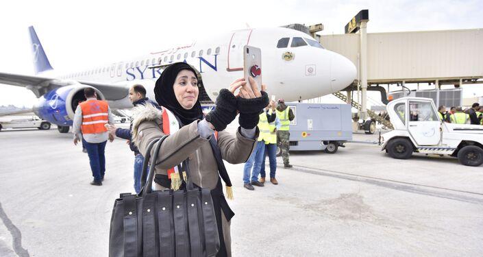 Mulher tirando foto no aeroporto de Damasco em dia do 1º voo de Damasco para Aleppo em 8 anos