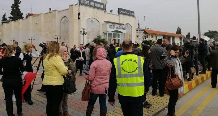Civis e funcionários esperando na área do aeroporto de Damasco