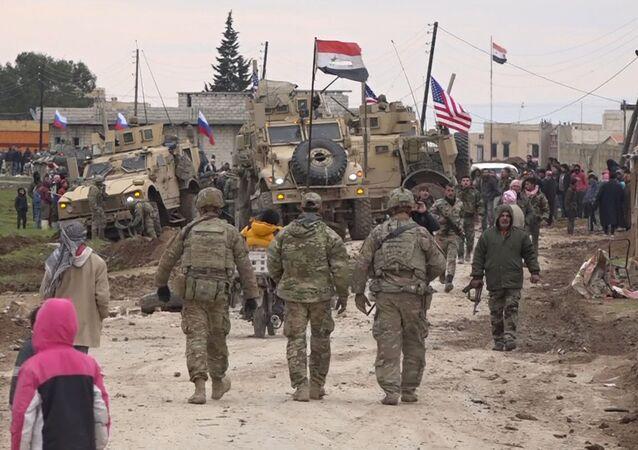 Soldados russos e sírios perto de comboio militar americano a leste da cidade de Qamishli, Síria, 12 de fevereiro de 2020