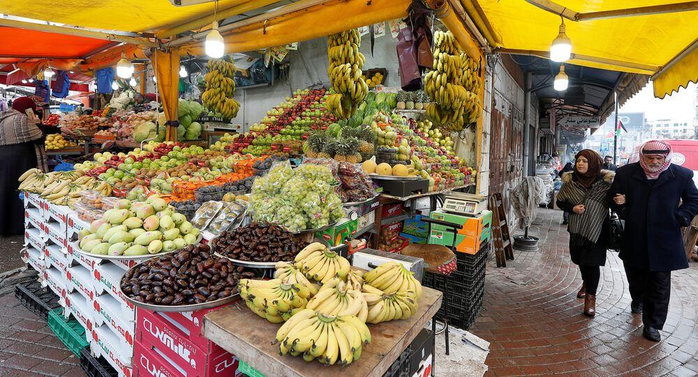 Palestinos caminham ao lado de barraca de frutas em mercado de Ramallah, na Cisjordânia