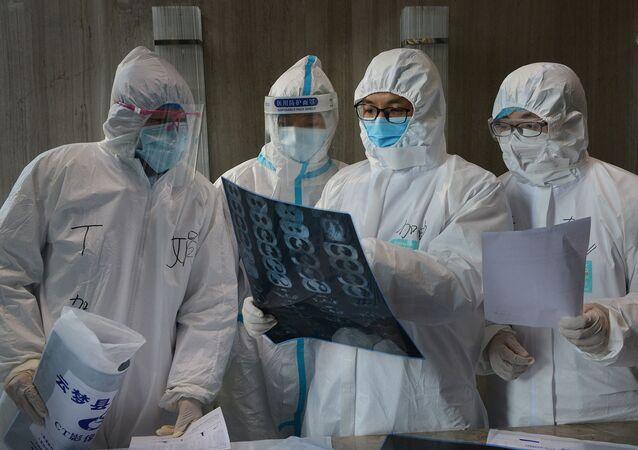 Médicos em trajes de proteção inspecionam imagem de tomografia computadorizada em hospital no município chinês de Yunmeng, em Hubei, a província mais atingida pelo novo surto de coronavírus, em 20 de fevereiro de 2020