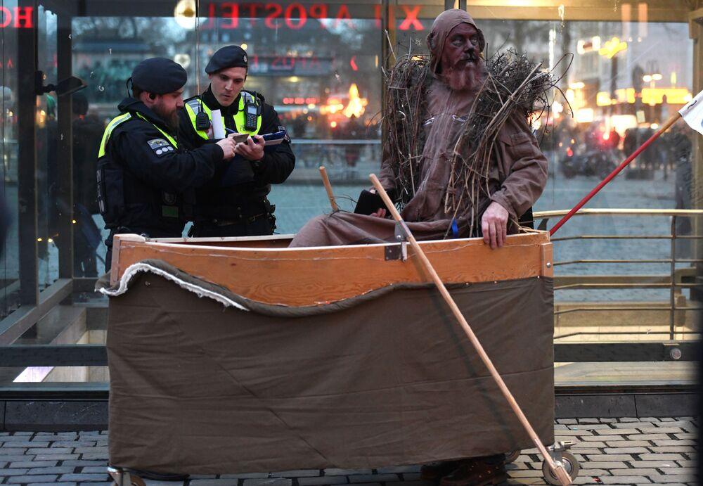 Policiais e manifestante durante ação em defesa do clima durante a celebração carnavalesca Geisterzug em Colônia, Alemanha