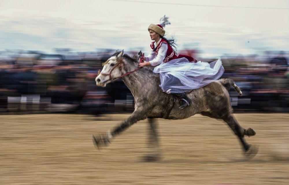 Mulher a cavalo durante o tradicional campeonato Kok-boru no Quirguistão