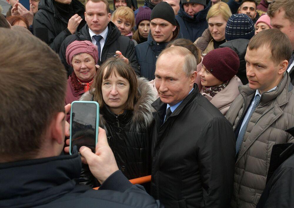 Presidente russo, Vladimir Putin, tira fotos com moradores de São Petersburgo após evento em memória do primeiro prefeito da cidade, Anatoly Sobchak
