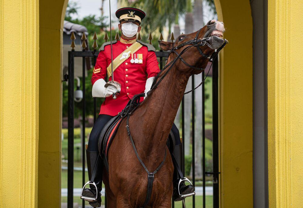 Soldado da Guarda Real malaia usando máscara no Palácio Nacional em Kuala Lumpur, Malásia