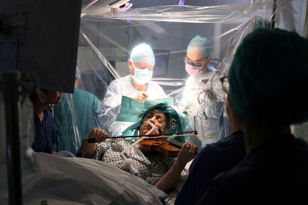 Paciente Dagmar Turner, 53, tocando violino enquanto médicos retiram um tumor de seu cérebro no hospital King's College, em Londres