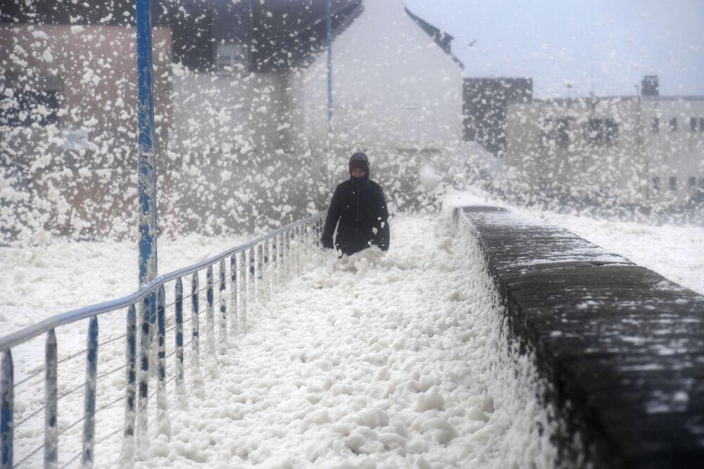 Homem caminhando em espuma marítima em Saint-Guénolé, França, enquanto tempestade Dennis atinge o país