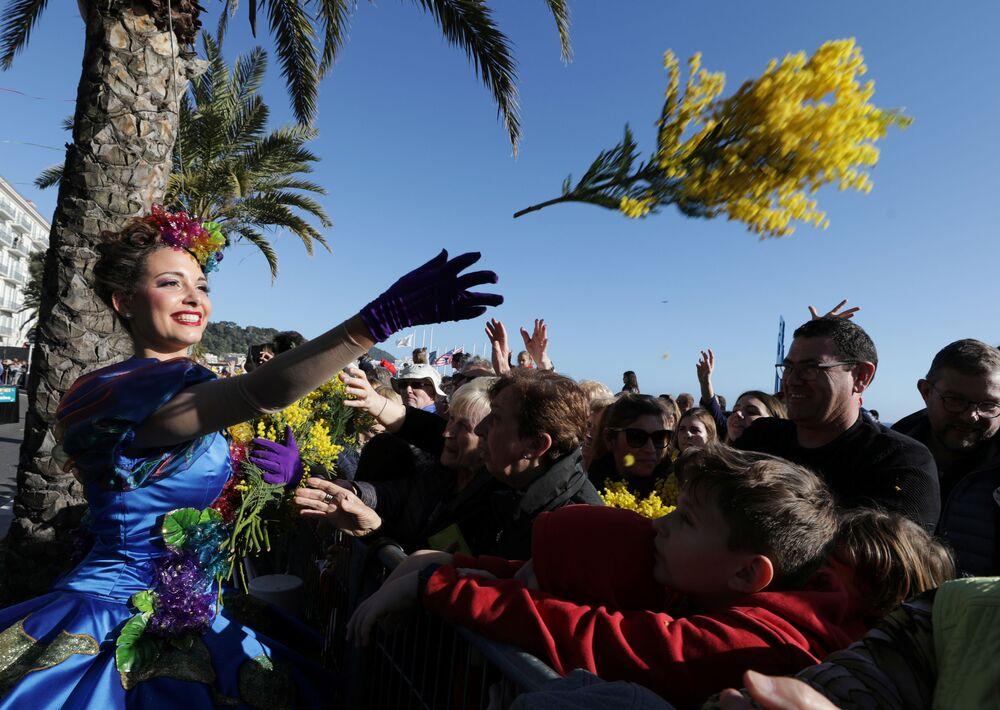Artista lança flores a populares durante a parada de flores na 136ª Parada de Carnaval em Nice, França